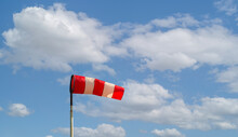Red And White Colored Windsock Against A Cloudy Sky. It's A Sunny Day In The Dutch Spring Season.