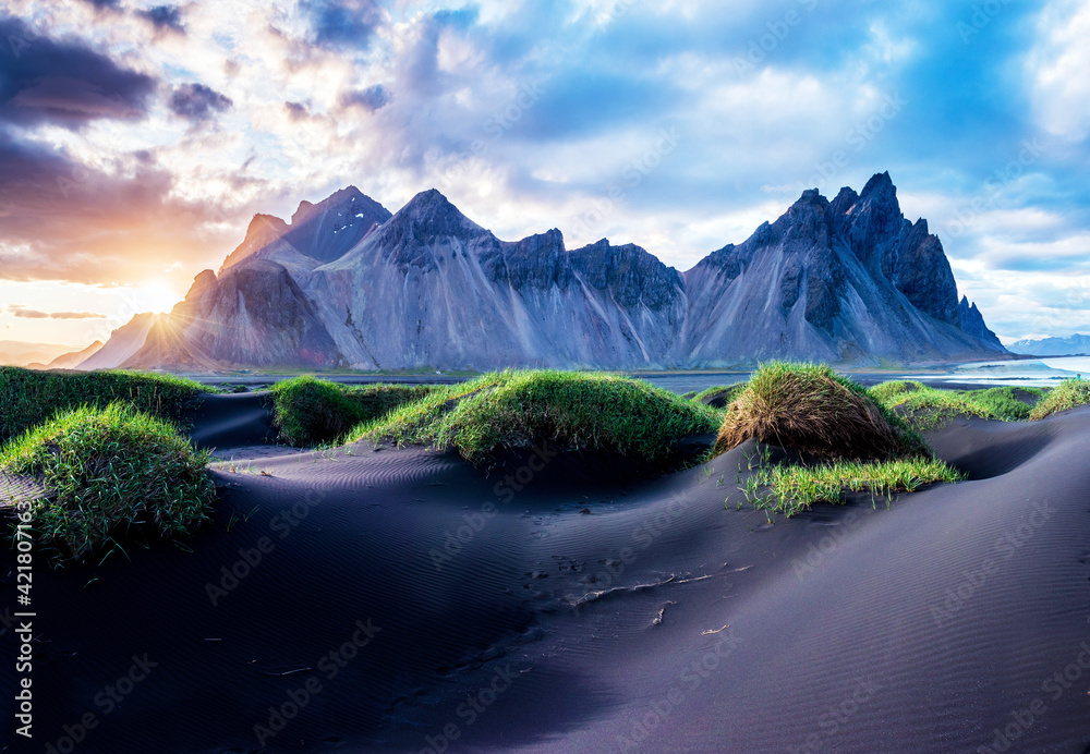 Fototapeta Scenic landscape with most beautiful mountains Vestrahorn on the Stokksnes peninsula and cozy lagoon with green grass on the sand dunes at sunset in Iceland. Exotic countries. Amazing places.