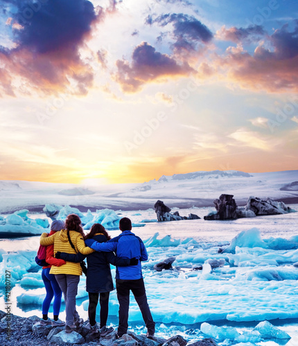 Four friends are looking at the sunset in the famous Jokulsarlon ice lagoon in Iceland. Exotic countries. Amazing places. (memories, impressions, rest, relaxation - concept) Wall mural