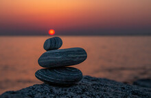 Balancing Stones On Rock Against Sea And Sky During Sunset