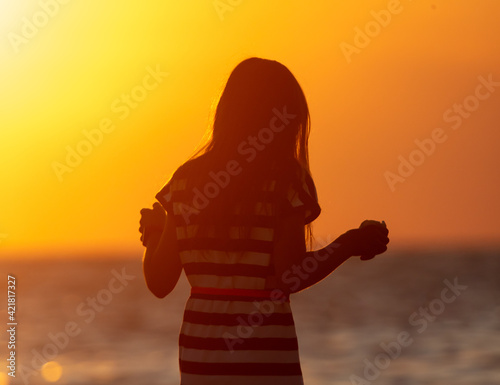 Silhouette of a girl in a dress by the sea