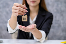 Image Of A Home Sales Woman Holding Key House. Real Estate Trading Concept.