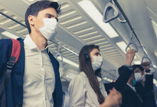 People On The Train Wear Anti-virus Masks And Travel During Rush Hours. Passengers Inside The Sky Train With The Masks On All People's Faces.