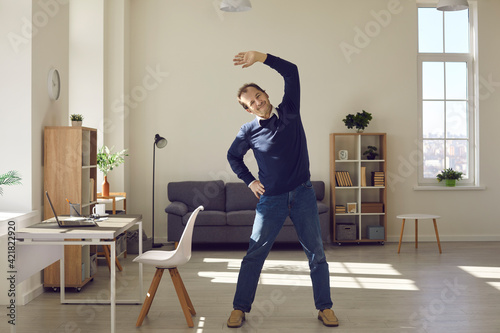 Fotografie, Obraz Happy middle aged man doing fitness exercise during working day at office workplace