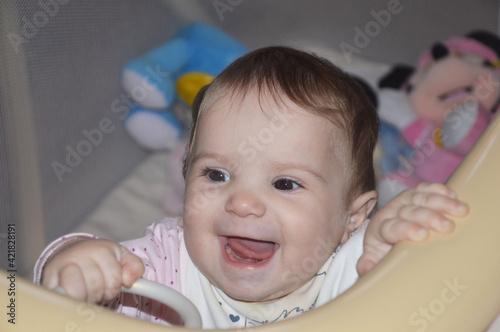 Fotografija Ritratto di una bambina di pochi mesi sorridente e tenera con gli occhi molto vivaci