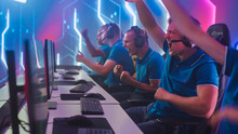 Diverse Esport Team Of Pro Gamers Play In Computer Video Game And Win Championship, Celebrate With YES Gestures. Stylish Design Cyber Games Arena. Online Streaming Of Tournament. Side View