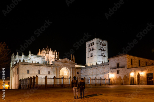 Beautiful shot of a male and female in front of Zamora Cathedral in Castile and Leon, S