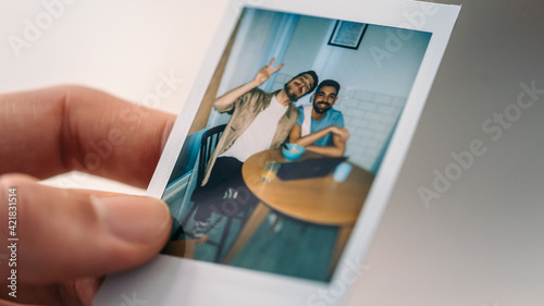 Obraz Close-up Hand Holding Photograph with Happy Couple or Friends, Posing, Having Fun on the Couch. Sentimental Memories, Reminding us of Goods Times, Happy Emotions about Our Friends and Loved ones. - fototapety do salonu