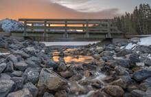Sunrise On A Pedestrian Bridge Over A Mountain Creek At Johnson Lake In Banff National Park, Alberta, Canada