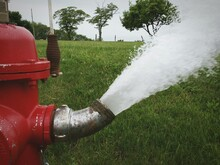 Water Gushing From Red Fire Hydrant Onto Green Grass On Rural Street