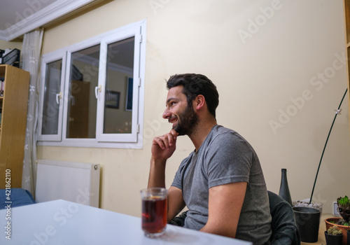 attractive young man smiles to his friends and tea glass on table at night home interior concept