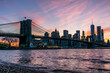 Brooklyn Bridge Over River With Buildings In Background At Sunset