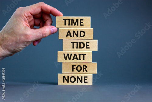 Obraz Time to action symbol. Wooden blocks with words time and tide wait for none. Beautiful grey background. Businessman hand. Business and time to action concept. Copy space. - fototapety do salonu
