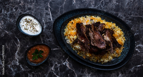 Fotografering A plate of kabsa rice and grilled lamb and two small plates of Yogurt and hot sauce