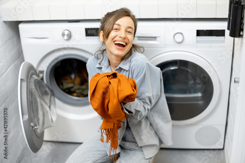 Fotografia Housewife with fresh cleaned scarf in the laundry room at home