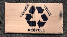 "Auf Pappe Gesprayter Slogan: ""REDUCE - REUSE - RECYCLE"""