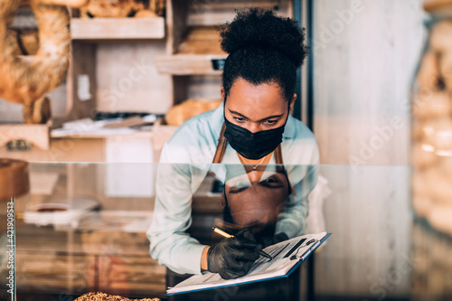 Fototapeta Bakery worker with face protective mask writes down orders for online delivery due to Coronavirus pandemic. obraz