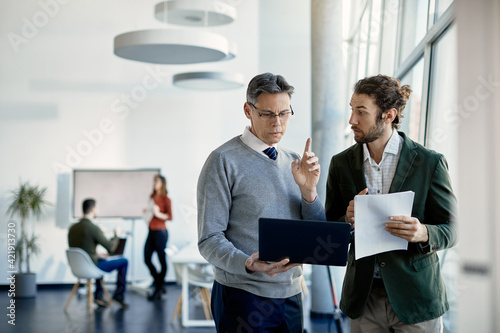 Young trainee discussing about data with mature business mentor who is using laptop in the office.