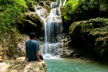 Backside View From A Young Asian Man Sitting On A Rock And Looks On The Waterfall