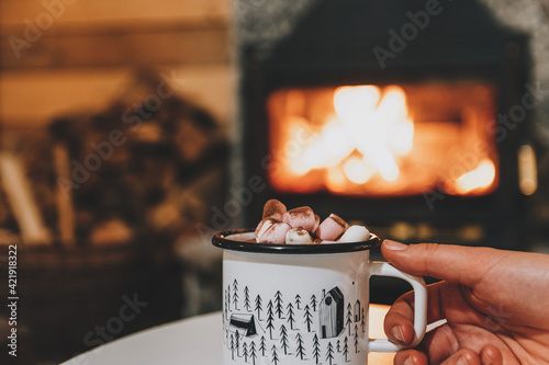 Papel de parede Woman's Hand Holding Cup Of Hot Drink In Front Of Fireplace In Cozy Cabin