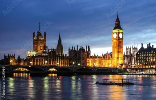 Fotografie, Obraz Illuminated Bridge Over River And Buildings In City