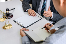 Midsection Of Lawyer Discussing With Businessman In Office