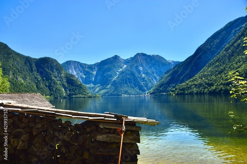 Scenic View With Boathouse, Lake And Mountains Against Clear Blue Sky Fototapet