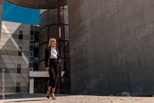 Young blonde business lady in formal clothing walking near the building Wallpaper Mural