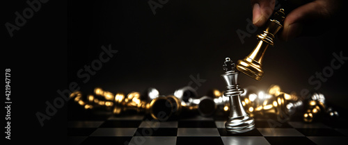 Fotografie, Obraz Close up hand choose king chess to challenge battle fighting on chess board concepts of leadership and business strategy and human personal organization risk management