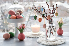 Easter Decorations On Windowsill In Spring. Wooden Painted Eggs On Pussy Willow Twigs In Glass Bottle, Easter Eggs In Rattan Basket, Rustic Ball, Macrame Mats. Gray Rainy Day, Rain Drops, Candle.