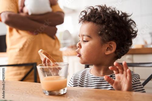 Fotografia Boy drinking orange juice at the breakfast at the kitchen