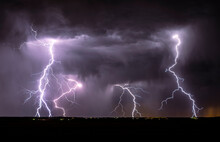 Lightning Streak From A Thunderstorm Cloud At Night In A Rural Setting. There Are Multiple Lightning Strikes Coming From The Thunderstorm.