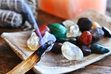 A Close Up Image Of A Burning Incense Stick And Healing Crystals.
