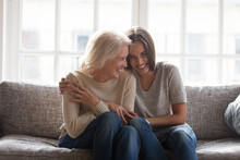 Smiling Adult Daughter And Mature 60s Mother Sit Relax On Sofa At Home Have Fun Laugh Enjoy Family Time Together. Happy Millennial Grownup Woman Child Cuddle Hug With Old Mom On Couch, Show Love Care.