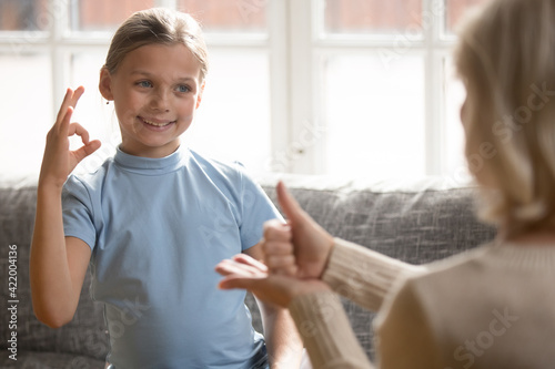 Happy deaf numb little teen girl child make hand gestures learn sign language with speech therapist. Smiling small disabled or impaired kid communicate teacher or coach. Children disability concept.