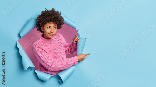 Fotografija Curly haired dark skinned young woman gives advice where to go indicates place for advertisement breaks through blue background wears knitted sweater recommends something