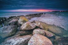 Long Breakwater At Cloudy Sunset