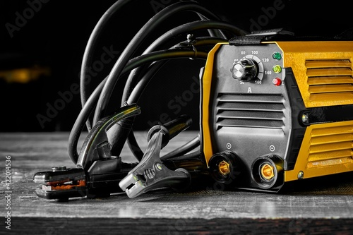 Obraz Inverter welding machine. Equipment for welding metals on a wooden desktop. - fototapety do salonu