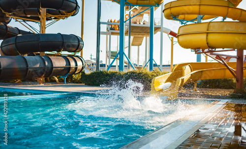 Obraz An woman descended from a slide into a pool with transparent water - fototapety do salonu