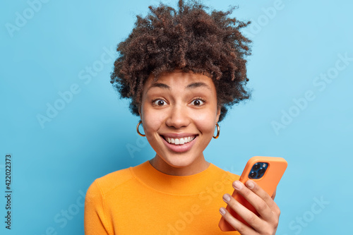 Portrait of good looking smiling young woman with curly hair uses mobile phone for chatting online downloads new app looks gladfully at camera wears orange jumper isolated over blue background