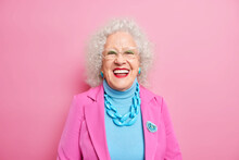 Portrait Of Aged Beautiful Woman With Curly Grey Hair Bright Makeup Smiles Happily Expresses Positive Emotions Dressed In Fashionable Outfit Isolated Over Pink Background. Positive Grandmother