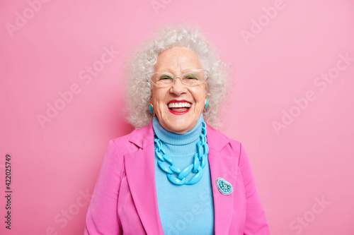 Tela Portrait of aged beautiful woman with curly grey hair bright makeup smiles happily expresses positive emotions dressed in fashionable outfit isolated over pink background