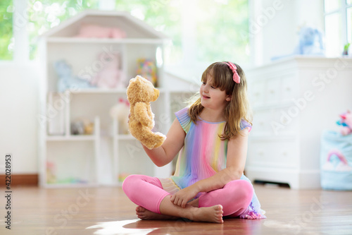 Fotografie, Obraz Little girl playing with doll house. Kid with toys