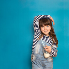 Cute Fashion Girl Drinks Nutritious Delicious Milk On A Straw And Stands On A Blue Background To Copy Space