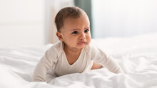 Portrait Of Sad Black Baby Crying And Crawling On Bed