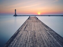Pier And Lighthouse Over Lake Against Sky During Sunrise