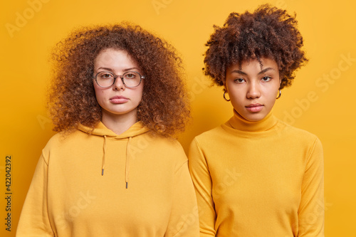 Fototapeta Horizontal shot of diverse female companions stand next to each other look serio