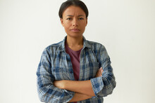 Portrait Of Casually Dressed Stubborn Young Dark Skinned Latin Woman Making Dissatisfied Facial Expression Frowning And Folding Arms, Her Look Expressing Suspicion, Distrust And Disagreement
