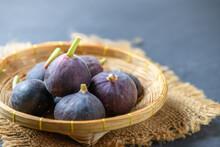Fresh Ripe Figs In Bamboo Basket On Dark Table. Healthy Mediterranean Fig Fruit.
