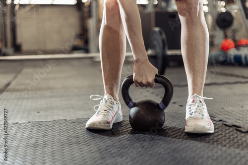 Fototapeta Woman's hand holding a heavy kettlebell in the gym obraz